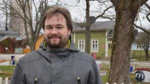 En man med brunt hår och skägg står framför en minigolfplan iklädd en grå jacka.