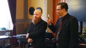 Två män står och håller i glas med skumvin framför andra människor.