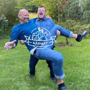 Två personer står och skrattar på en gräsmatta