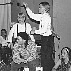 Joukko nuoria, yksi istuu rumpujen takana, kolme nuorta etualalla, valkopaitainen kitaristi taustalla ja toinen valkopaitainen johtaa näkymättömissä olevaa kuoroa.