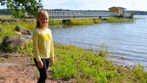 En flicka som står på stranden framför vattnet och en lång brygga.
