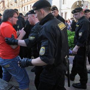 Vitrysk polis håller i en demonstrant som i sin tur försöker förklara något.