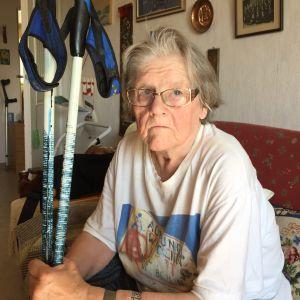En äldre kvinna som sitter på en soffa och håller i ett par stavar.