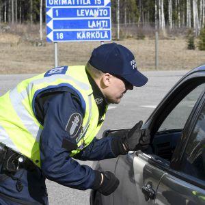 Polisen ställer frågor till en bilist.