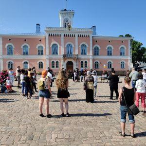 Flera personer står i solskenet på Lovisa torg.