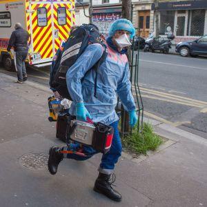 Ambulanspersonal ska vårda en patient i Paris som uppvisat symptom på covid-19.