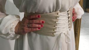 En vit klänning med korsettbälte.