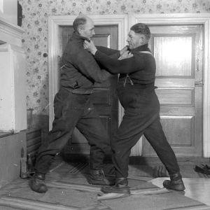 """Två män leker """"kragtag"""", där man ska försöka lägga sin motståndare på rygg, Man får bara hålla i den andras krage. Bilden är tagen 1937 i Korsnäs, Harrström."""