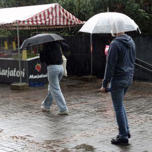 Två personer med paraply över huvudet går på en regnfylld gata i Helsingfors. De går förbi ett bärstånd.