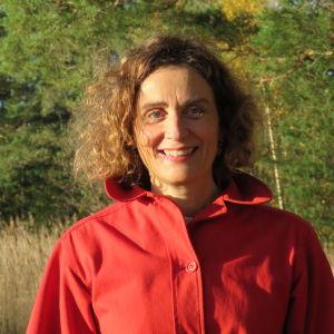 En kvinna med halvlångt, mörkt lockigt hår och röd jacka. Rött läppstift. Ler och ser in i kameran. Tallskog i bakgrunden och lite gulbrun vass.