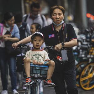 En pappa som leder sin cykel med sitt barn som sitter i cykelkorgen.