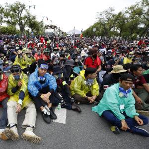 Suuri ihmisjoukko istuu kadulla.