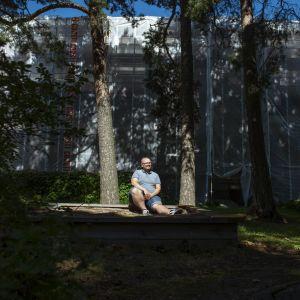 Benjamin Molini huputetun kotinsa edessä Haagassa hiekkalaatikon reunalla istumassa. Talossa on käynnissä iso julkisivuremontti.