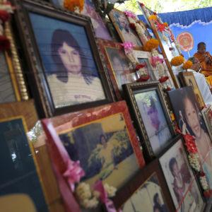Thailändska buddhistmunkar ber invid fotografier på tsunamioffer i Baan Nam Khem i Phang Nga i Thailand.