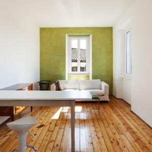 Ett vardagsrum med träplanksgolv. Ett fönster längs bak med en vit soffa framför. Ett vitt bord med en vit stol i förgrunden.