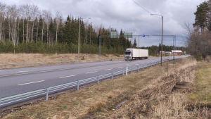 En långtradare på en annars tom asfalterad väg.
