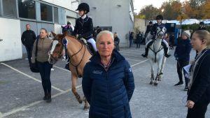 Kristiina 'Jepa' Idman framför två hästar med ryttare.