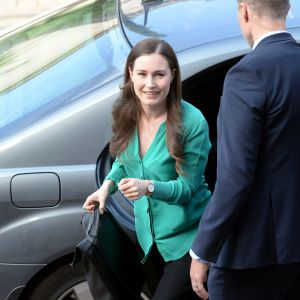 Sanna Marin stiger leende ut ur en svart bil.