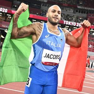 Lamont Marcell Jacobs firar seger med italienska flaggan.