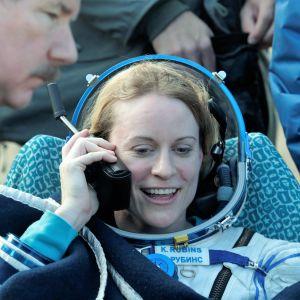 Kate Rubins puhuu satelliittipuhelimeen laskeutumisen jälkeen. Hänellä on yllään avaruuspuku. Ympärillä hyörii ihmisiä.