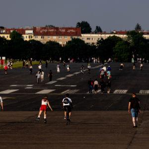 Människor promenerar på den föredetta landningsbanan på Tempelhof i Berlin. I bakgrunden syns en rad med hus.