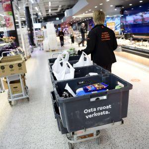 En person i citymarket-uniform drar en kärra med matlådor inne i en matbutik.