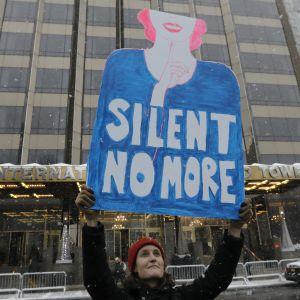 Kvinna med metoo-skylt demonstrerar mot tystnadskulturen i New York.