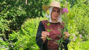 En kvinna håller upp två växter.