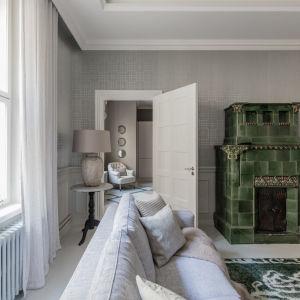Ett vardagsrum med en grön kakelugn i jugendstil.