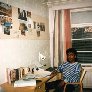 Nuori srilankalainen mies istuu kirjoituspöydän ääressä valkotiiliseinäisessä huoneessa.