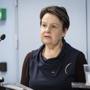 En kvinna i medelåldern med kort mörkt hår och mörka kläder ser allvarlig ut och ser ut att prata där hon står framför en mikrofon och tittar snett ut ur bilden.