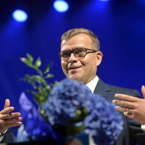En man (Petteri Orpo) med glasögon. Mannen har en blå blombukett framför sig.