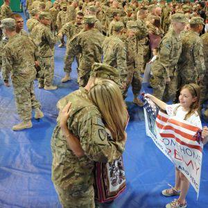 Amerikkalainen sotilas halaa vaimoaan, sotilaan tytär odottaa vieressä tervetulolipun kanssa.