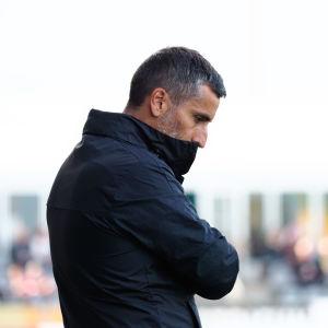 José Riveiroi svart jacka blickar neråt mot gräset under match.