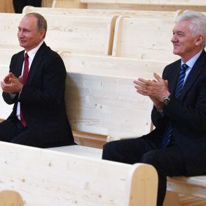 Vladimir Putin och Gennadij Timtjenko sitter bredvid varandra och applåderar.