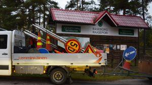 Vägmärken på ett flak framför skylten som välkomnar besökaren till Raseborg.