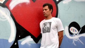 Man i vit t-skjort framför gatukonstverk.