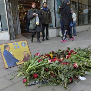 Blommor vid Olof Palmes mordplats och tavla av Palme och Anna Lindh.