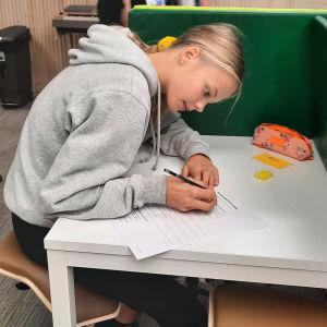 Barn sitter vid skrivbord och skriver på papper.
