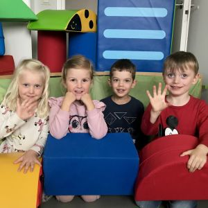 Fyra barn bland färgglada kuddar.