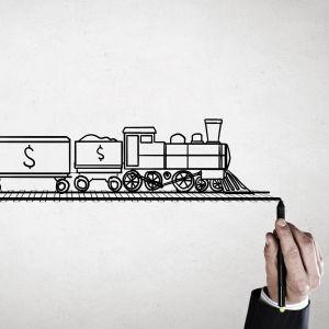 En hand ritar en järnvägsbana och ett ritat tåg ned dollartecken på kör på banan.