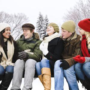 Tre kvinnor och två män sitter på bänk och talar, det är snöigt och alla har vinterkläder på sig
