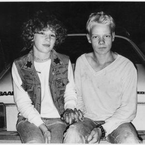 Nuoripari istuu Saabin takapuskurin päällä ja pitää toisiaan kädestä.