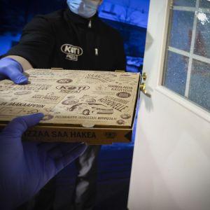Kotiin tuodaan pizza ravintolasta. Koronan aikaan maski kasvoilla-