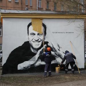 Arbetare målar över en väggmålning av Aleksej Navalnyj.