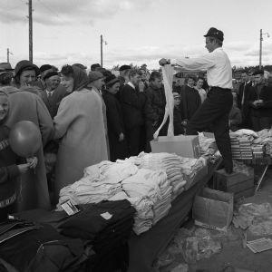 En svartvit bild av en man som vid ett försäljningstånd håller upp ett par långkalsonger för människor som går förbi.