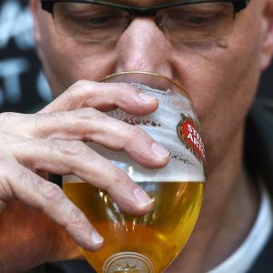 En man dricker öl.
