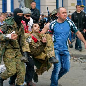 Proryska demonstranter transporterar en sårad man.