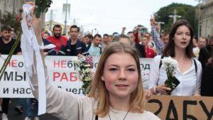 En blond kvinna håller upp en bukett med vita blommor i ett demonstrationståg i Belarus.