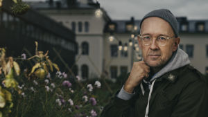 Författaren Johan Kling invid blommor. 2019.